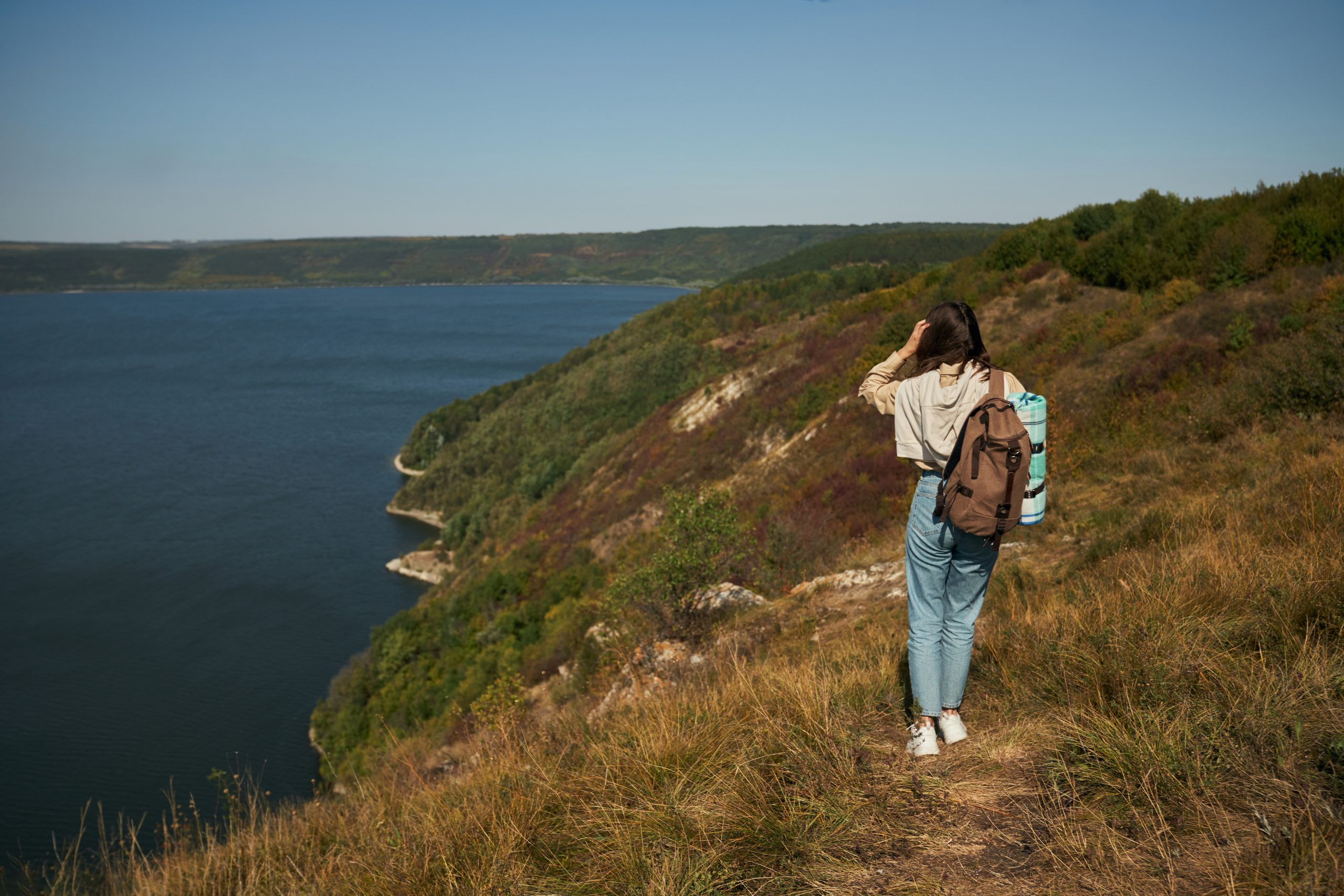 woman-with-backpack-walking-along-high-green-hill-scaled.jpg