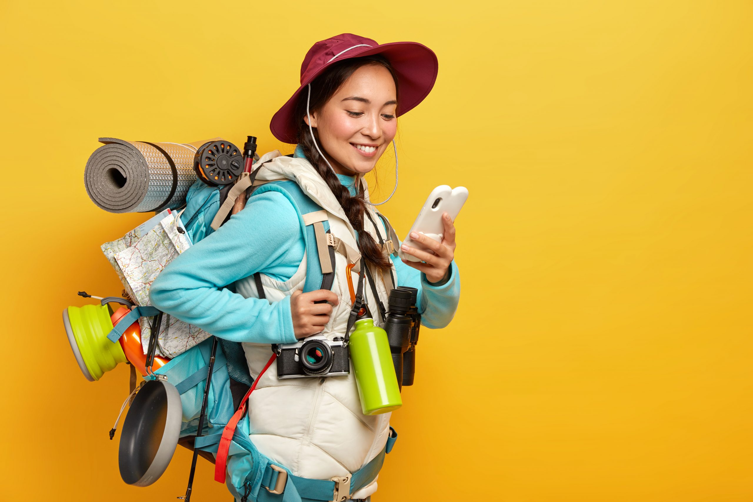 positive-pretty-asian-tourist-uses-modern-gadget-navigating-dressed-hat-jumper-with-jacket-uses-binoculars-retro-camera-karemat-during-trip-stands-against-yellow-wall-scaled.jpg