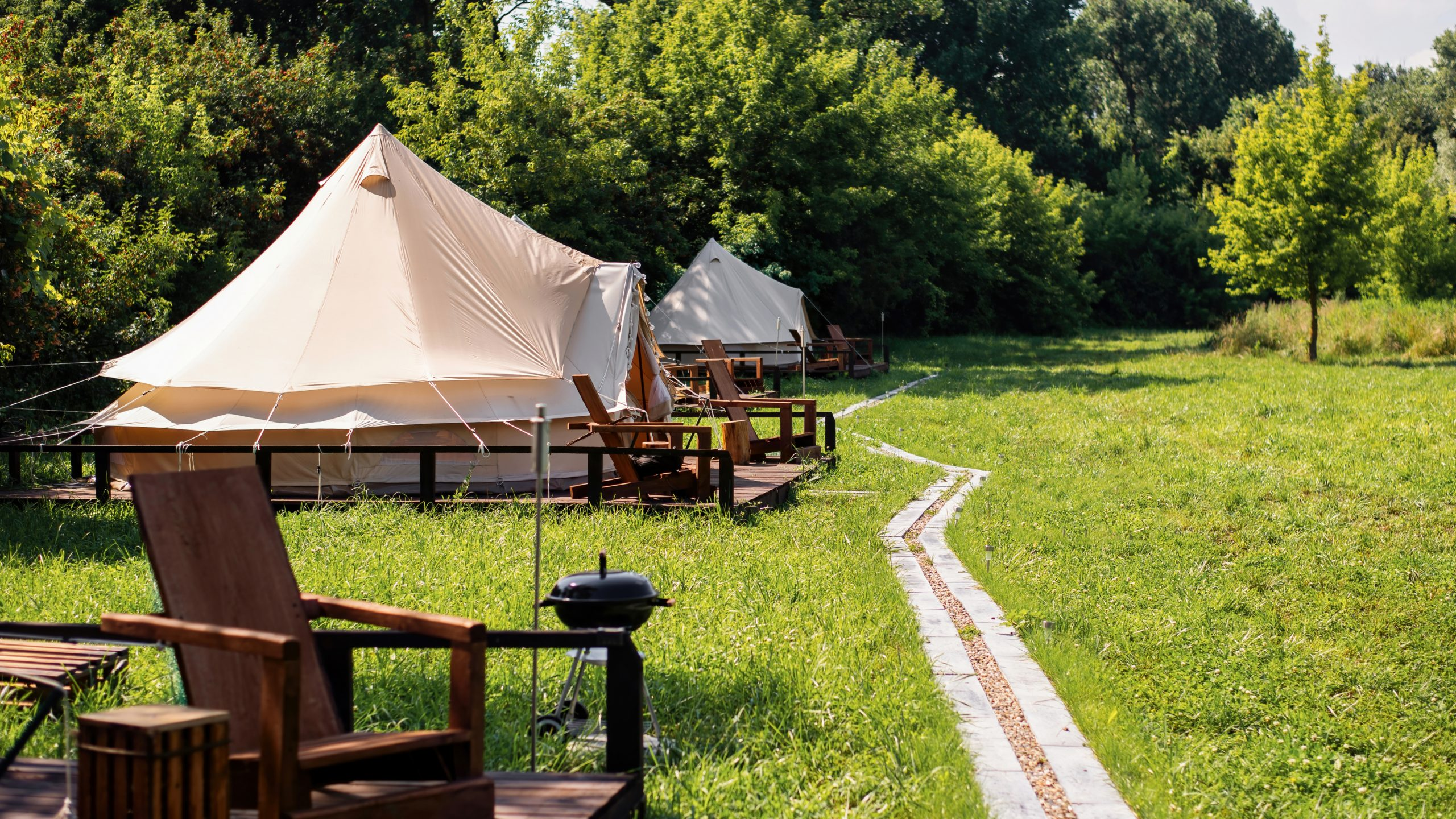 tents-with-wooden-chairs-pathway-front-them-glamping-nature-greenery-around-scaled.jpg